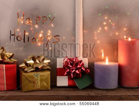 Happy Holidays written in the frost of a window with Christmas lights on the outside of the window. In front of the window are presents and lighted candles bathed in warm light. Horizontal format.
