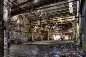 interior of am abandoned factory with rubble and debris - desolate room of an old destroyed industrial warehouse - hdr image poster