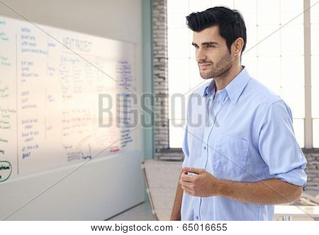 Caucasian male officeworker thinking in whiteboard room of office, smiling.