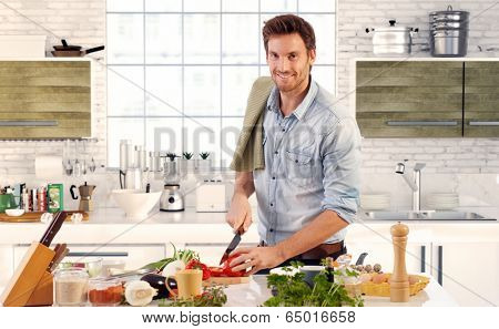 Happy handsome man cooking in kitchen at home.