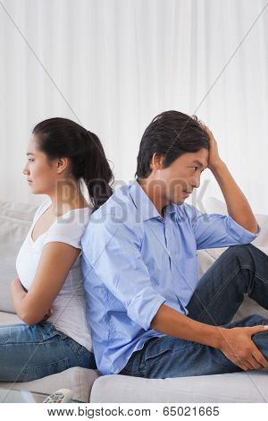 Couple not talking after a dispute on the sofa at home in the living room