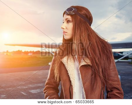 Portrait of young beautiful woman pilot in front of airplane. poster