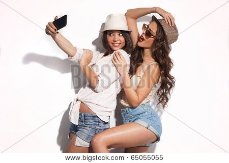 two young women taking selfie with mobile phone  poster