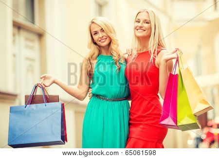 sale, tourism, shopping and happy people concept - two beautiful women with shopping bags in the ctiy