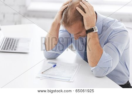 business, office, school and education concept - stressed businessman with papers at work