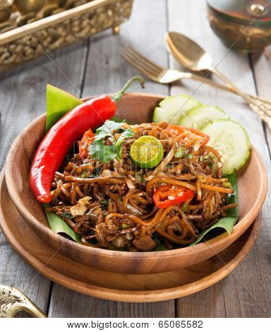 Asian spicy fried noodles, ready to serve on dining table.