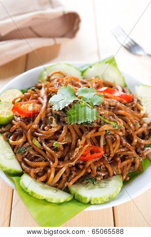 Asian style spicy fried noodles, ready to serve on dining table.