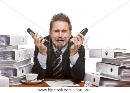 Stressed Business Man  With Two Telephones Is Cryoing In Office