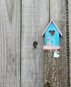 Teal blue and pink birdhouse (Family and Friends) with wood heart perched on top of wooden post poster
