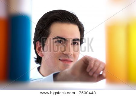 Collage student looks in bookshelf