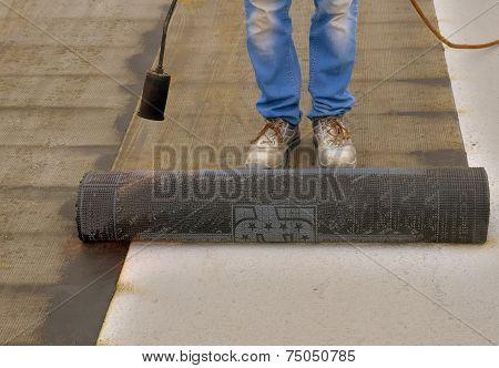 Worker preparing part of bitumen roofing felt