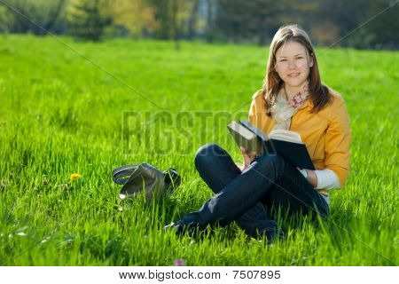 Girl With Book On The Grass
