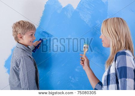 Mother And Son Having Fun From Painting The Wall