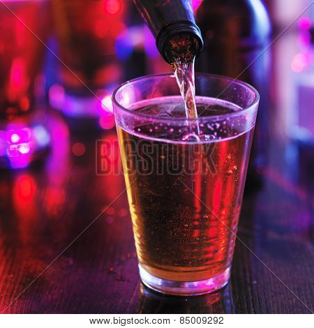 filling glass with beer from the bottle in colorful bar, lighting is super colorful to represent lighting you would see in a club or pub.