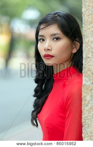 Attractive serious young Vietnamese woman in a vivid red dress leaning on a wall in an urban street turning to look at the camera, close up view of her face