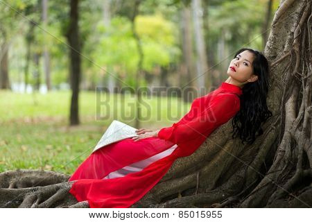 Pretty slim young Vietnamese lady dressed in red traditional clothes relaxing on aerial tree roots in a public park reclining on her back as she stares thoughtfully into the air