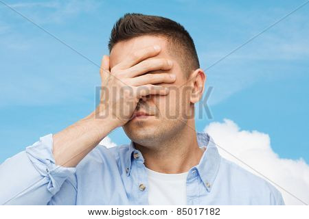 stress, headache, health care and people concept - unhappy man covering his eyes by hand over blue sky and cloud background