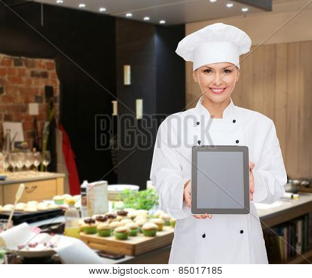 cooking, bakery, people, technology and food concept - smiling female chef, cook or baker showing tablet pc computer blank screen over restaurant kitchen background
