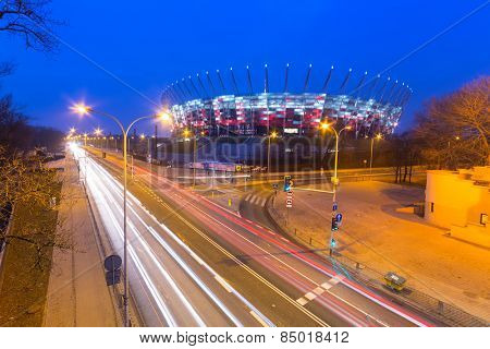 WARSAW, POLAND - 27 FEBRUARY 2014: National Stadium in Warsaw illuminated at night by national colors, Poland. The National Stadium is a retractable roof football stadium for 58 145 spectators.