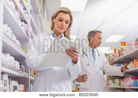 Young trainee writing on a prescription pad in the pharmacy