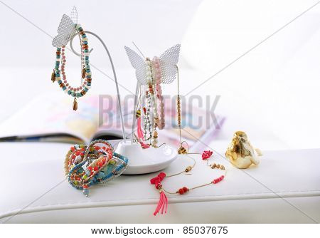 Decorative stand with jewelry and bijouterie on sofa in room