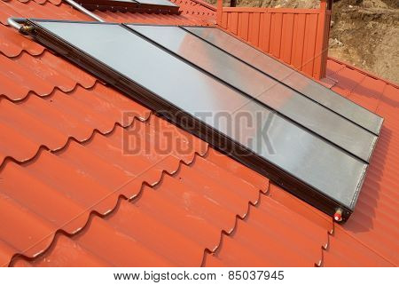 Solar water heating system on the red roof. Gelio panels. poster