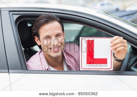Learner driver smiling and holding l plate in his car