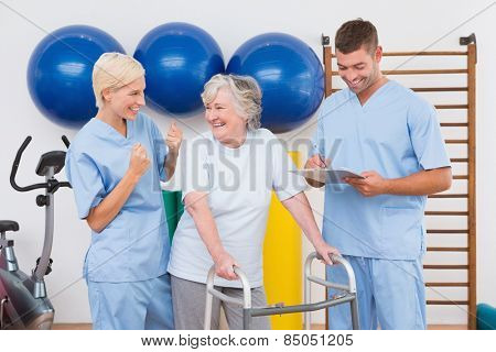 Therapists with invalid senior woman in fitness studio