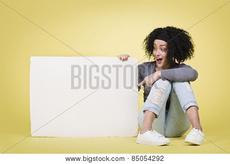 Happy delighted girl pointing at a blank white paper sign board with empty copy space, isolated on yellow background.