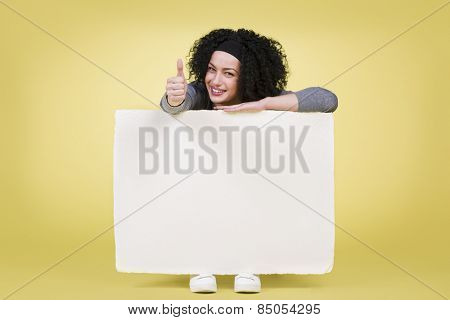 Happy girl holding a white blank paper sign board with empty copy space and giving thumbs up, isolated on yellow background.
