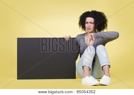 Unhappy woman being discontent presenting a blank black paper sign board with copy space, isolated on yellow background.