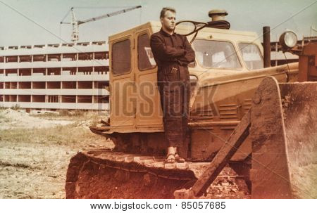 Vintage photo of young man standing on excavator (1960's)