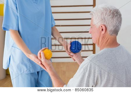 Senior man working out with his therapist in fitness studio