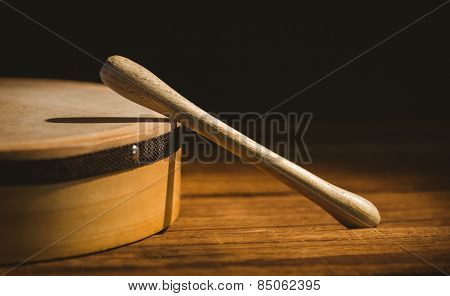 Traditional Irish bodhran and stick on wooden table