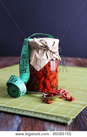 Goji berries in glass bottle wrapped with paper on wooden table and dark background