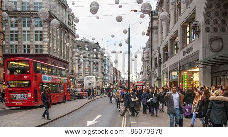 Regent street, Oxford circus with lots of pedestrians and cars, taxis on the road.