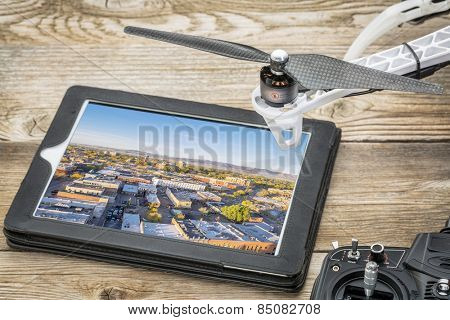 drone aerial photography concept - reviewing aerial pictures of Fort Collins downtown on a digital tablet with a drone rotor and radio control transmitter,