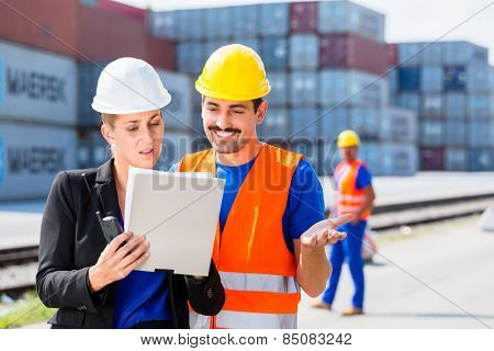 Manager with clipboard full of freight documents talking with worker on shipment yard in front of container