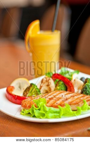 Tasty dish of salmon steak with vegetables and juice poster