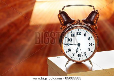 Retro alarm clock in bedroom early morning. First sunrays in your bed, a new day begins.