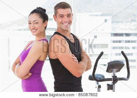 Fit couple smiling at camera with arms crossed in fitness studio
