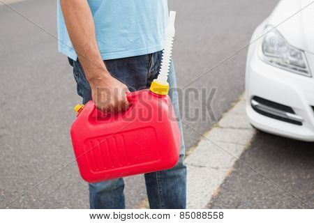 Man bringing petrol canister to a broken down car in the street