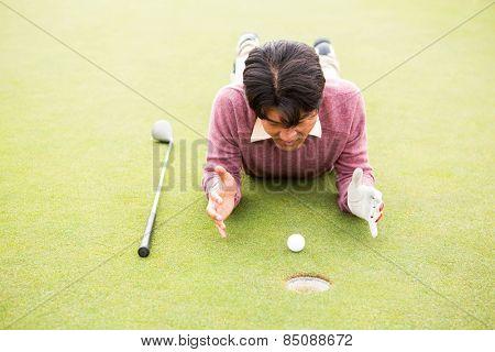 Golfer lying near golf ball at golf course