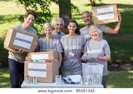 Happy volunteer family holding donations boxes on a sunny day