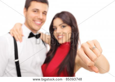 Woman posing with her fianc�©e and showing her engagement ring with the focus on the ring isolated on white background