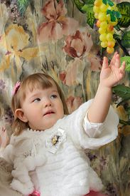 Beautiful little girl in a white fur vest
