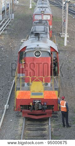 Shunting Locomotive Standing On Rails At The Train Station. Nearby Stands A Railway Worker In overa