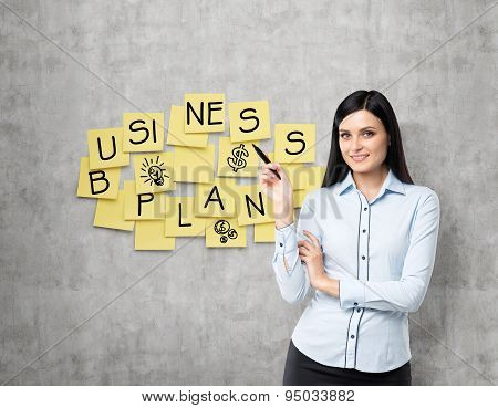 Brunette Lade Shows The New Business Plan. Yellow Stickers Are Hanged On The Concrete Wall.