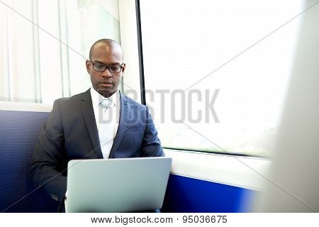 Young Businessman In A Train Using Laptop Computer