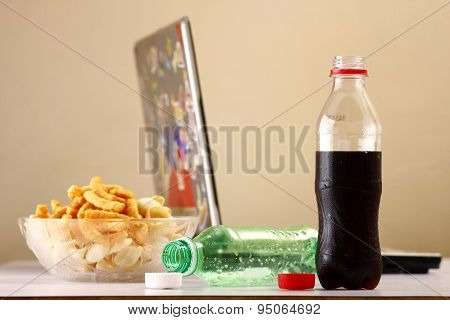 Bottles of softdrinks or soda, chips and a laptop computer in the background